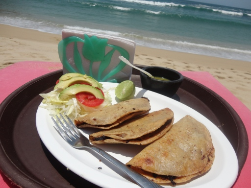 Greasy, though delicious fried fish tacos, on the beach