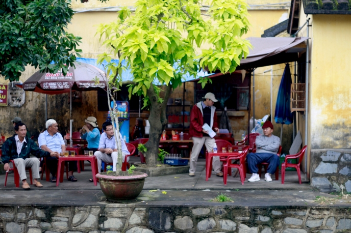 Vietnamese men sitting around on plastic furniture, drinking coffee; a very common sight.