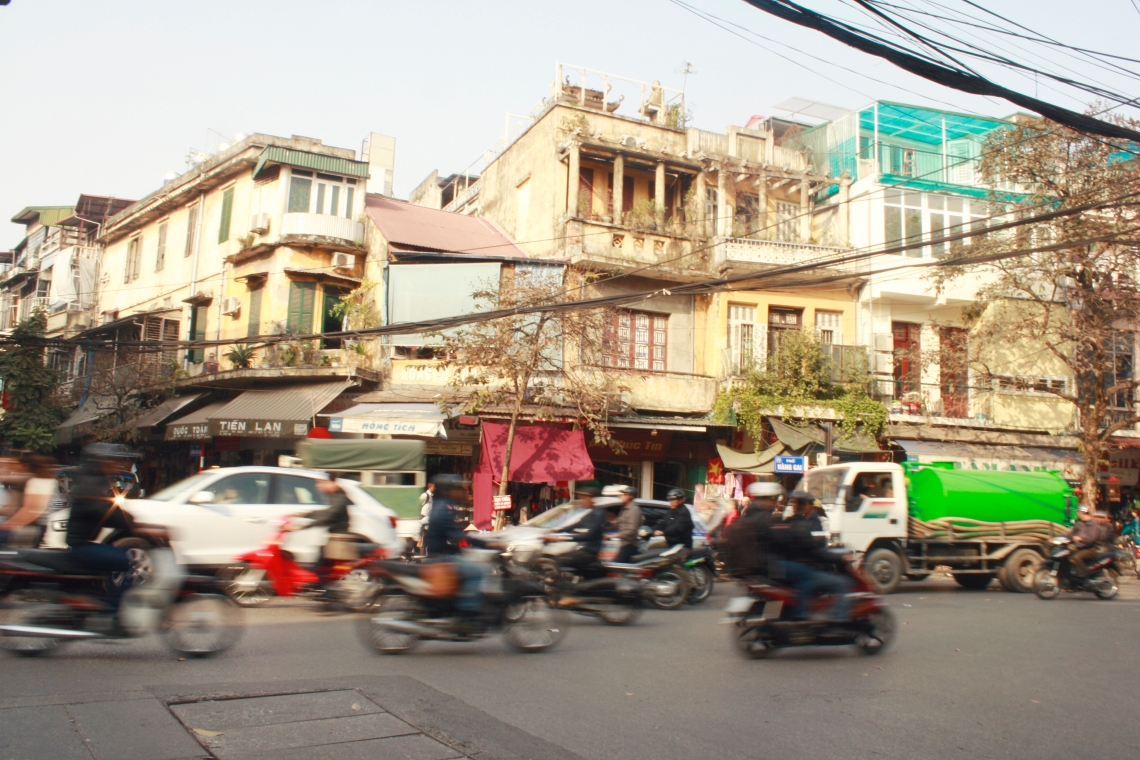 Cars and motorbikes wizzing by in Hanoi